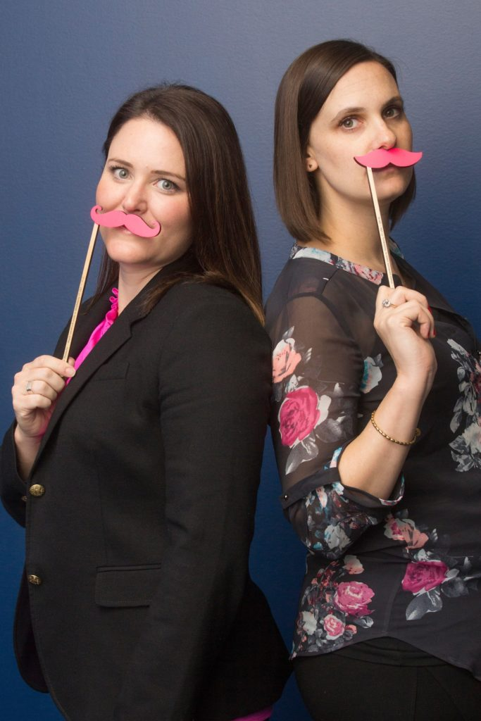 Two women, back-to-back, holding up pink Lyft moustaches
