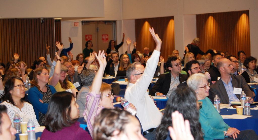 People raising hands to ask questions at a forum.