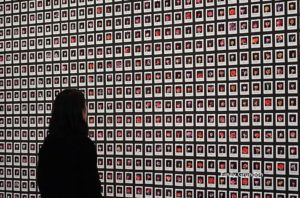 a woman looks at an AI art project, which is a wall of small images